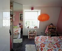 Modern child's room with pillow-shaped, orange lamp and reflection of flowered bed linen in fitted wardrobe