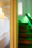 Glowing green lights integrated into handrail of a stairway next to a white-tiled bathroom