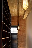 Ceiling-height, empty shelving and light bulb lamps in front of brick wall with factory window in English loft apartment