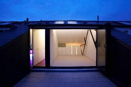Roof terrace at dusk with view of illuminated, empty interior with white fitted cupboards