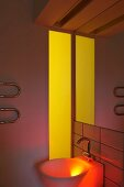 Sink niche illuminated in coloured light by yellow interior window