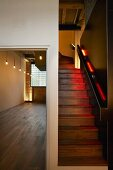 Centrally installed stairway, indirectly illuminated with coloured light in a London loft apartment with wooden floors and industrial glass windows