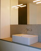 Rectangular sit-on basin with wall-mounted taps concealed in grey wall cladding under a large mirror reflecting lights