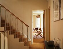 Wall-to-wall sisal carpeting in hall with staircase and adjacent dining room