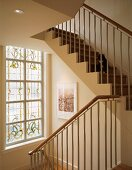 Plain, modern apartment staircase with stepped, white facings in front of window with floral, stained, leaded glass