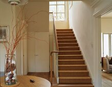 Foyer of English house with sisal stair carpet and vase with gathered natural materials