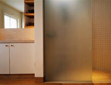 Frosted glass shower partition in bathroom with stone tiles and wooden flooring