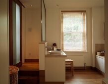 Sliding door and wooden steps to sunken bathroom in warm natural shades