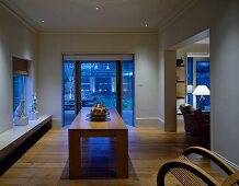 Twilight in open-plan living-dining room with solid wood table and unusual wooden rocking chair