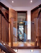 View through reflective glass panel of balustrade - hall with floor to ceiling wooden doors in an English house