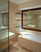 Glass shelves in front of room-width mirror with wooden frame above a stone-clad bathtub