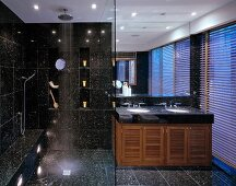 Black speckled tiles in modern bathroom with spotlight effects, ceiling-height mirror and blinds on twilit window