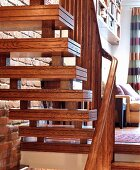 Wooden stairs with treads ornamented with double grooves and wooden balustrade in living room