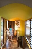 Woman in hallway with wooden floor and yellow walls