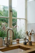 Wooden worktop with kitchen sink and vintage tap fittings in front of window