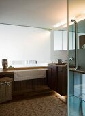 View through open glass door of wood-clad bathtub and washstand in modern bathroom