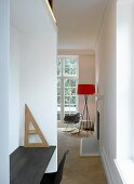 Modern office niche and view through narrow opening to standard lamp in minimalistic room