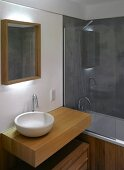 Modern washstand with white ceramic bowl on wooden pedestal and bathtub behind a glass partition