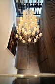 View of retro ceiling light with multiple shades in modern hallway with dark wooden wall