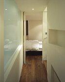 Modern hallway with open bedroom door and view of bed