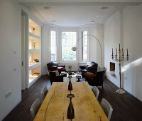 Open-plan living with rustic wooden table and antique leather armchairs in bay window