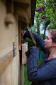 Frau holt Eier aus dem Nest im Hühnerstall