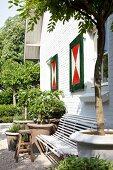 weiße Gartenbank und Tontöpfe mit Grünpflanzen vor Wohnhaus mit weisser Backsteinfassade und rotgrün bemalten Fensterläden
