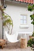 Weisser Fledermausstuhl im Stil der 50er Jahre und Baumstammhocker vor weißem Backsteinhaus mit rankender Glyzinie