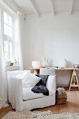 Weisser Atelierwohnraum mit Hussensessel vor hohem Sprossenfenster und Keramikvasen auf einer Tischplatte im Hintergrund