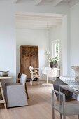 Weisser Wohnraum in renoviertem Landhaus mit Gefäßen auf drei Tischen unterschiedlicher Stilrichtung und altem Holzschrank im Hintergrund