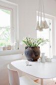 Kontrastierender dunkler Tonkrug mit Blumen auf modernem Tisch und verschiedene Keramik in strahlend weißem Landhausambiente
