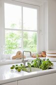 Moderne, weisse Küche in renoviertem Landhaus mit einem Strauss Mohnblumen in der Spüle, Uhr und Holzschalen im Hintergrund