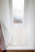 Blick von oben auf den Abgang einer weissen Landhaustreppe mit Milchglasfenster zum gegenüberliegenden Raum