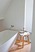 Holzschemel mit Seifenschale und Handtuch neben freistehender Designerbadewanne im ausgebauten Dach