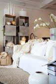 Sammlung ausgefallener Vasen in Wohnzimmer mit gemütlichem Sofa und kubischem Edelstahlregal im Hintergund