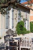 Sonnenbeschienenes Terrassenplätzchen mit Holzstühlen vor traditionellem Landhaus mit hellgrauen Fensterläden an hohen Fenstern