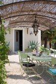 Hellgrün lackierte Metallstühle und Tisch im Retrostil unter Pergola mit Strohdach vor mediterranem Wohnhaus