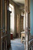 Blick durch offene Tür in Wohnraum auf antik rustikalem Vitrinenschrank in altem herrschaftlichen Landhaus