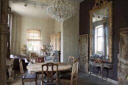 Stilmix in schlichtem offenen Wohn-Essraum mit rustikalem Holztisch und antiken Stühlen gegenüber Rokoko Konsolentisch unter Wandspiegel mit Goldrahmen