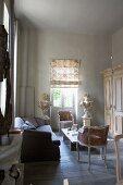 Salonbereich mit Rokokostühlen und moderner Couch um rustikalem Bodentisch in schlichtem Ambiente
