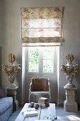 Stilisierte Vasen auf Stelen in antik griechischem Stil und Rokokostuhl am Fenster mit halbgeschlossenem Faltrollo
