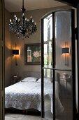 Glastür mit Metallrahmen und Blick auf Kerzenleuchter an Decke über Bett in schlichtem Schlafzimmer mit ländlichem Flair