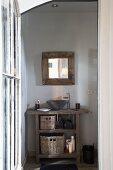 Blick durch offene Tür auf rustikalen Waschtisch mit aufgesetzter Keramikschüssel neben Designerarmatur und auf Wandspiegel