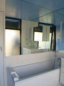 Modern bathroom with bathtub beneath large mirror on wall