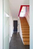Treppenaufgang im minimalistischen Flur mit Natursteinboden