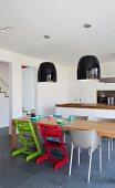 Roter und Grüner Kinderstuhl vor massiven Holztisch in offener Küche