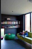 Wohnzimmer mit Natursteinboden und grüner Couch vor Fensterfront