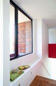 Blick durch grosses Fenster mit Fensterbank auf Backsteinfassade