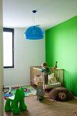 Grüne Wand im Kinderzimmer mit Kinderbett und blaue Halbkreislampe