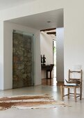 Contemporary architecture with wall section of uncut stones presented as work of art behind glass panel